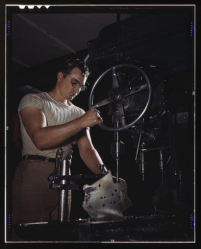 "An employee in the drill-press section of North American's huge machine shop runs mounting holes in a large dural casting, Inglewood, Calif. This plant produces the battle-tested B-25 (""Billy Mitchell"") bomber, used in General Doolittle's raid on Tokyo, a"